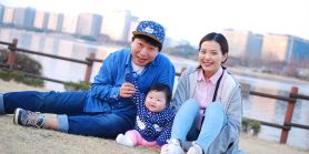 Asian parents and their infant sit together, smiling