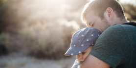 Father hugs child in the sunlight