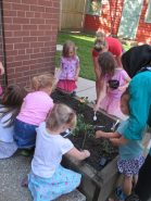 Children gardening together, with guidance from educators and caregivers